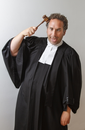 Man in canadian laywer robe tapping a gavel on his head with a dumb face expression