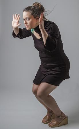 agachado: mujer en su thirtie agachándose por debajo de algo invisible