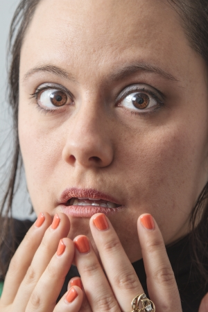 perplex: close-up portrait of a thirtie something brunette woman with hand over her mouth and a puzzled look Stock Photo