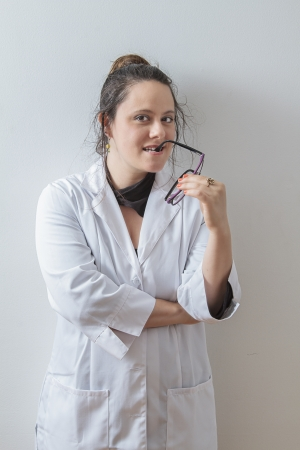 thirtie something brunette woman wearing a lab coat and glasses arm in her mouth photo