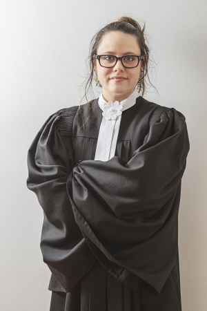 female judge: thirtie something brunette woman wearing a canadian lawyer toga with wispy hair Stock Photo
