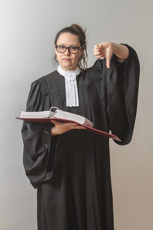 thirty something brunette woman wearing a canadian lawyer toga with a red criminal law book in hand with her thumb down