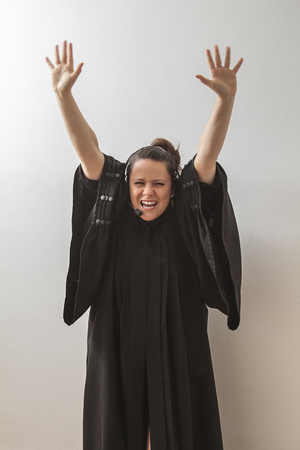 thirty something brunette woman dress as a preacher with her arm in the air