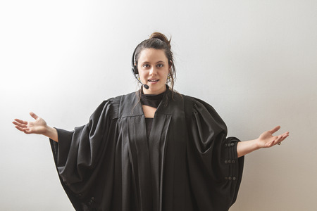 thirty something brunette woman dress as a preacher with her arm opened Stock Photo