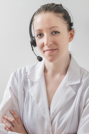 twenty something woman wearing a lab coat, a headset and great smile and , against a white wall photo