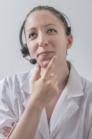 twenty something female doctor wearing a lab coat and a headset, thinking about the anwser to a question photo