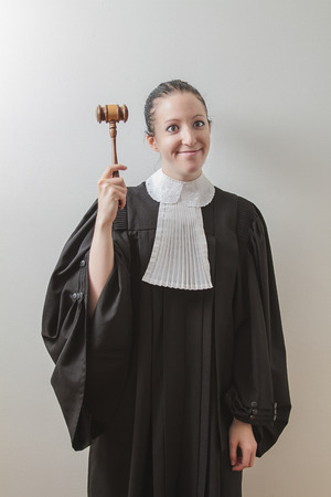 twenty something woman wearing a canadian lawyer toga, banging a gavel on her head and crossing her eyes photo