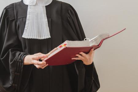 giurisprudenza: avvocato canadese in toga, leggendo da un libro di diritto rosso