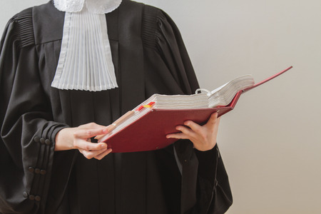 canadian lawyer in toga, reading from a red law book Stock Photo
