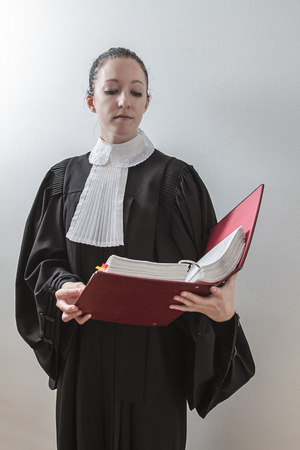 twenty something woman wearing a canadian lawyer toga, reading from a red law book Stock Photo