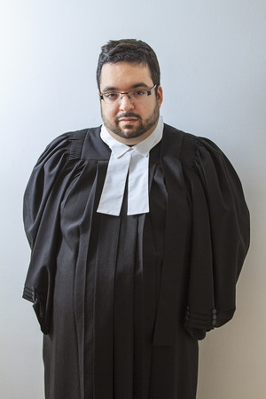 Man wearing a judge toga with hand behind his back photo