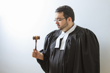 Man wearing a judge toga looking at a gavel photo