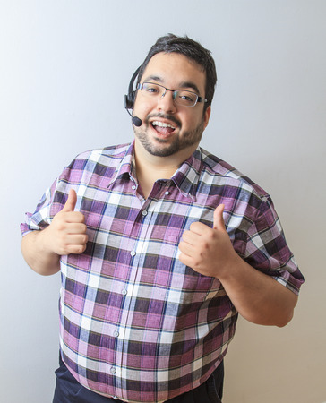 customer service representative: Late twenty year old man with phone headset and his thumb up in sign of approval Stock Photo