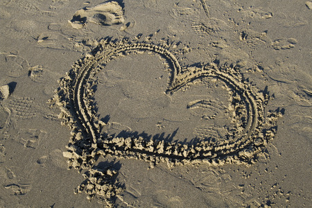 heart drawn into the sand photo