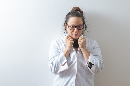 Woman doctor holding up her collar and leaning against a white wall photo