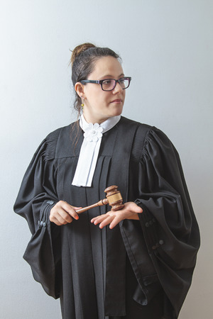 statute: thirty something brunette woman wearing a canadian lawyer toga with a gavel in her hands