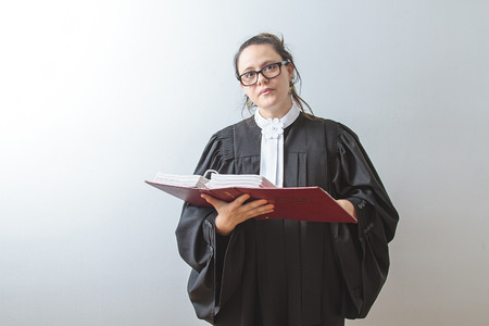 thirty something brunette woman wearing a canadian lawyer toga reading a red criminal law book