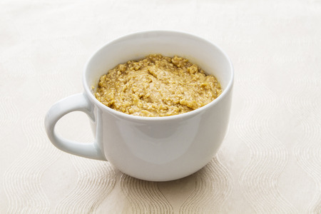 cup filled with oatmal on a apron