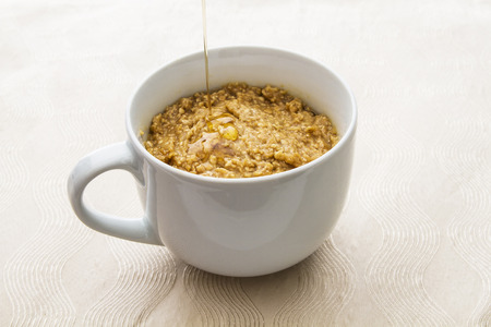 cup filled with oatmal with maple syrup being poured on top photo