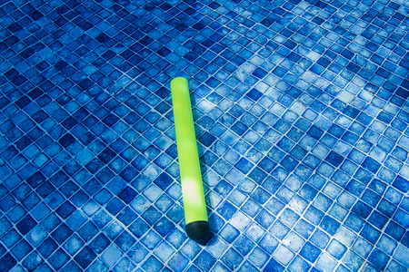 glow stick: glow stick toy at the bottom of a pool