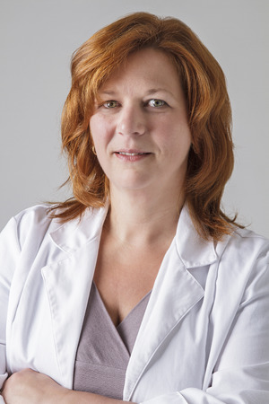 forty year old woman with red hair wearing a doctor lab coat Stock Photo