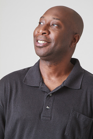 old black man: forty year old black man, wearing a black polo, looking up