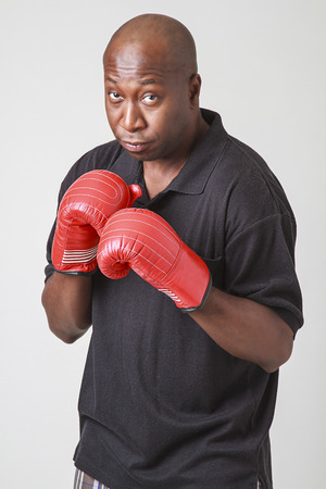 old black man: Forty year old black man, wearing a black polo and red boxing glove, holding his arm up in guard position