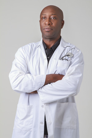 old black man: Forty year old black man, wearing a lab coat with a stethoscop in his pocket