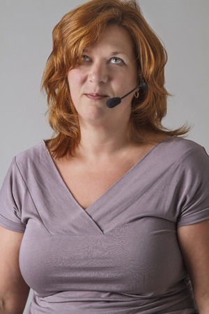 forty year old woman with red hair with headset looking up in annoyance photo