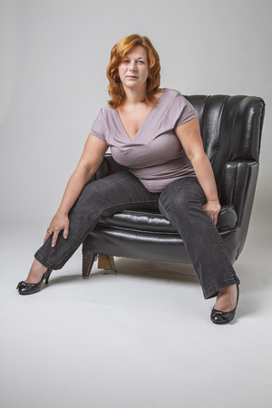 40 year old woman: 40 year old woman with red hair and round body type, sitting in a love seat