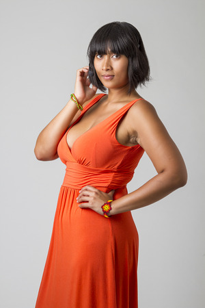 low cut: asian woman, wearing a low cut orange dress and a headset