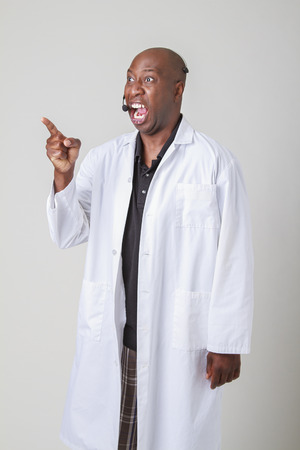 Forty year old black man, wearing a lab coat and a telephone headset, pointing and screaming at something photo