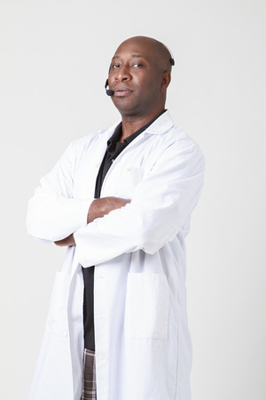 Forty year old black man, wearing a lab coat with telephone headset on his head photo