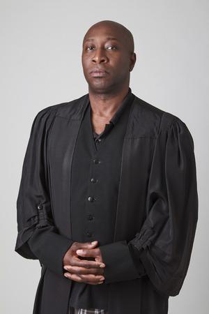 bald black man wearing a preacher toga