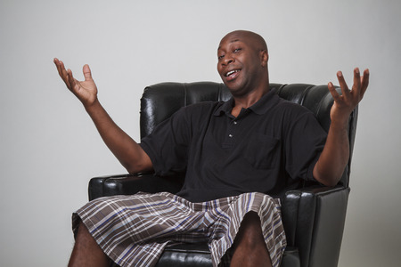 old black man: Forty year old black man, sitting on a leather chair, with his arm in the air and a smile