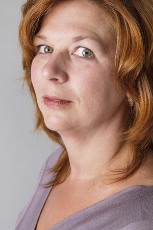 forty something: forty something woman with red hair with a small look of fear Stock Photo