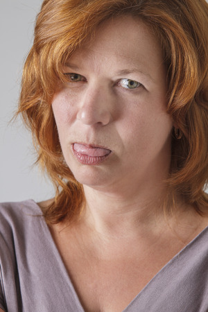 annoyance: mid-fortied woman with red hair, showing her tongue in annoyance Stock Photo