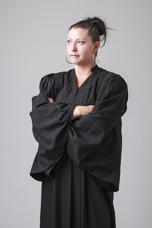 thirty something: thirty something woman, wearing a preacher robe, with a serious expression