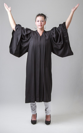 thirty something woman, wearing a preacher robe, with her arms in the air