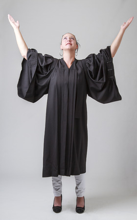 thirty something: thirty something woman, wearing a preacher robe, with her arms up Stock Photo