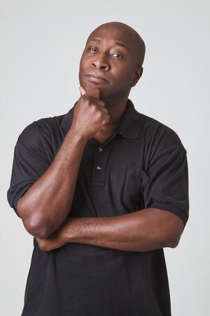 forty something: forty something bald black man thinking about something Stock Photo