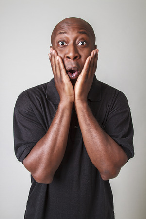 forty year old bald black man holding his face with surprise expression