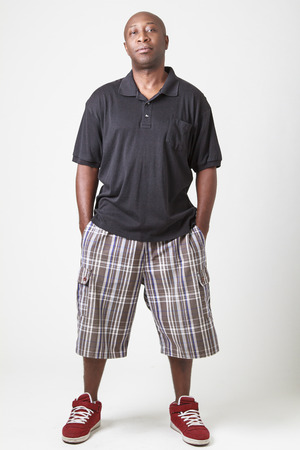 forty something: forty something bald black man wearing a black polo, gray shirt and red sneakers