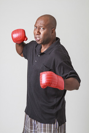forty something: forty something bald black man wearing a black polo and red boxing gloves, throwing a punch