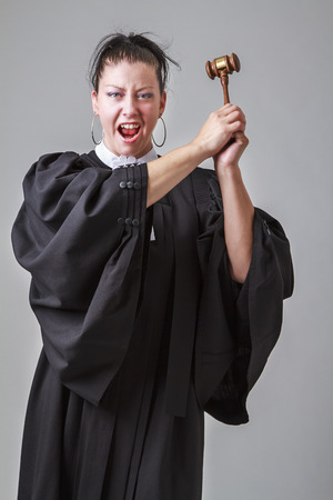 thirties: Woman in her thirties wearing a canadian lawyer toga, screaming with a gavel in the air Stock Photo