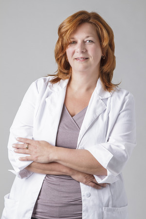 forty something: forty something woman doctocr with red hair, against a gray background