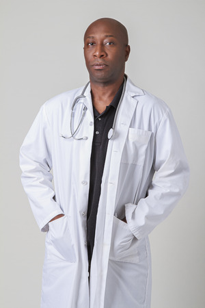 forty something: forty something bald black man wearing a lab coat and stethoscope Stock Photo