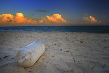 beach buoy: dirty white buoy resting on a sandy beach Stock Photo