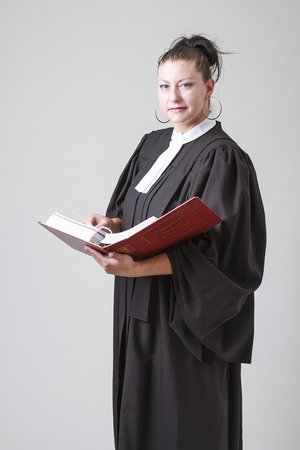 Woman lawyer holding an opened red law book Stock Photo