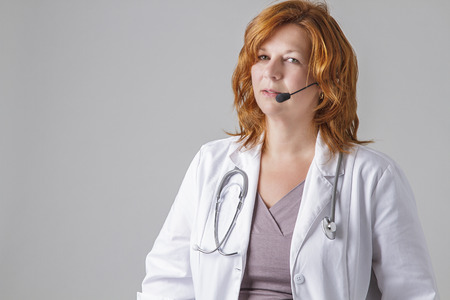 forty something: forty something woman doctor with red hair with a stethoscope and a headset